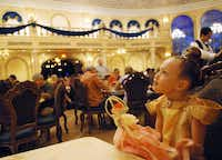 Rosie Pramik at the Be Our Guest Restaurant, where chandeliers hang from a ceiling painted with cherubs floating among the clouds.