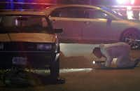 A forensic service officer examined one of four corpses at a crime scene in Monterrey last month.