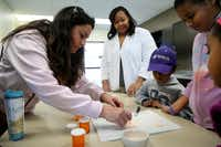 Parent Tina Hitchcock fills a tablet with crushed up Tums in the Pharmacy Tech program at an open house at Dubiski Career High School.