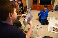 Jake Oxford, 12, (left) and his brother, Luke, 8, organize newspaper clippings about their youngest brother, Nate, at their Fate home. Nate battled a rare form of brain cancer for more than half of his life and died Jan. 28, about two weeks before his seventh birthday.The clippings will be displayed at Nate's memorial at 7 p.m. at Lake Pointe Church, 701 E. Interstate 30, Rockwall.