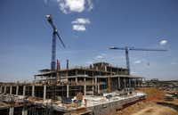 Construction continues on the new Parkland Memorial Hospital even as patient-safety lapses found by federal inspectors place millions of dollars in federal health care funding in jeopardy.