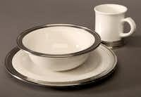 Elegant dining: Handmade by artisans in Italy, Convivio dinnerware by Match is white ceramic rimmed in hand -stamped pewter of 95 percent tin content. Dishwasher safe. 11-inch dinner plate $107; 9.8-inch soup bowl $100; mug $71 at The Ivy House, Dallas.