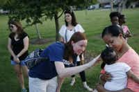 Mindy Brown (left) greets Addison Hunt, the 3-month-old daughter of Angela Hunt (right), before participating in Tuesday's prayer vigil in the Craig Ranch neighborhood of McKinney. (Andy Jacobsohn/The Dallas Morning News)