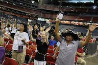 "From left: Yolanda Sanchez of Wylie, Mary Joe Cason of Terrell, and Danise Holcomb of Houston raise their hands in prayer before ""The Response"" on Saturday at Reliant Stadium in Houston."