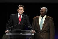 "Pastor C.L. Jackson (right) prays along with Gov. Rick Perry during ""The Response"" on Saturday at Reliant Stadium in Houston."