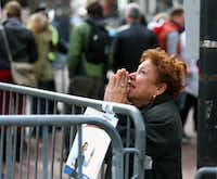 """A distraught woman kneels in prayer after the explosions. """"There are so many people without legs,"""" one runner said. """"It's all blood. There's blood everywhere.""""John Tlumacki - The Boston Globe"""