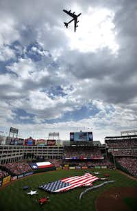A B-52 named Cajun Fear from Barksdale Air Force Base in Louisiana performs a flyover during the national anthem; a flag in the shape of the U.S. covers the outfield.