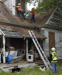 Workers from Johnson Roofing helped board up windows in a home across the field from the fertilizer plant that exploded in West.