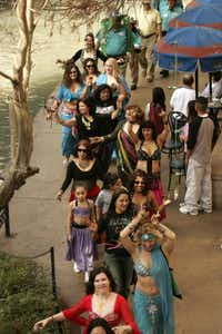 A troupe of belly dancers makes its way along the River Walk during the 2006 Mud Parade.