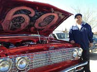 """Joe Ruiz posed proudly next to his cherry red 1987 Chevy truck, which is dressed up with parts from a 1960 Impala. The hood is popped open to reveal the truck's name, painted on the inside: """"69."""""""