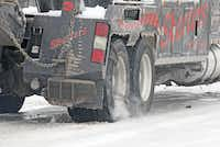 A tow truck spun its chained wheels while trying to get a semi-truck over the bridge Saturday at FM455 on I-35 southbound in Sanger after an ice storm swept through.