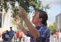 """Sara Holland prays to """"lift up the name of Jesus,"""" near the federal courthouse in Austin.Reshma Kirpalani  -  Statesman.com"""