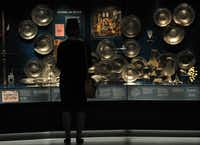 A museum employee stands next to pewter plates found on the wreck of the Tudor warship Mary Rose at the Mary Rose Museum in Portsmouth, Hampshire, southern England.
