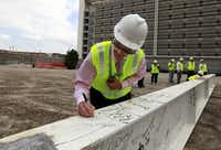 Roberto de la Cruz, a member of the Parkland board, signed his name on a beam at the construction site of the new Parkland hospital in October.