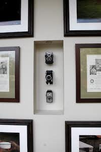 A hallway with photographer Jeremy Lock's photographs and cameras at the home of D'Andra Simmons and Jeremy Lock in Dallas.
