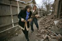 Belinda Ortiz (left) and Leisa McClelland grabbed bricks as souvenirs before Monday morning's demolition of the 1925 apartment building at 600 Elsbeth St. in north Oak Cliff where Lee Harvey Oswald once lived.