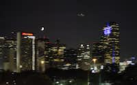 A plane carrying out aerial spraying to kill mosquitos and control the spread of  West Nile virus flies over Central Expressway just east of downtown Dallas Monday night.