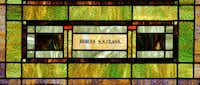 A dedication to a Sunday School class of years past is etched into original  stained glass windows.