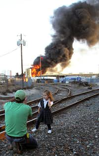 Kevin Cromer snapped a photo of his daughter Cason Cromer as flames and smoke filled the sky Friday.