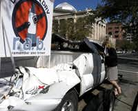 State Rep. Susan King, R-Houston, looks in the windows of Alex Brown's truck, which was parked outside the Capitol in March to illustrate the dangers of texting and driving. Brown, a Lubbock-area teen, was texting when she lost control of her truck in November 2009 and was killed on her way to school.