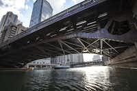 Tour boats glide beneath the Dearborn Street Bridge in Chicago, Ill.