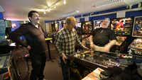 In this Dec. 16, 2013 photo, out-of-state visitors Jeff Goldsmith, left, Jim Lindquist, center, and Dave Socha, right, play the PIN BOT pinball machine, which was released in 1986, as they visit the Seattle Pinball Museum in Seattle.