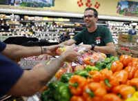 Jason Brick (right) and Jay Tome work on a produce display at Trader Joe's in Plano on September 6, 2012.