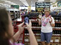 Adawndria Fisher, Dallas takes a photo of Deborah McClure, of The Colony holding Charles Shaw (Two Buck Chuck) wine during a grand opening at Trader Joe's in Plano on September 7, 2012. McClure doesn't drink wine but just recently heard about Two Buck Chuck and wanted to take a photo of it to send to her friend in California.