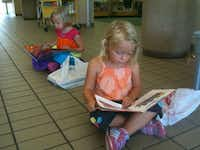Two children read from books they selected at a recent book sale by the Friends of the Irving Public Library.