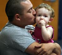 Army E4 James Torres gave daughter Khloe a kiss as they watched events on Wednesday.