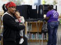 Crystal Coleman (left) holds her daughter, Christani Turner, while waiting to vote Tuesday morning at Sherrod Elementary School in Arlington.David Woo