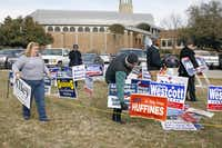 Barbara Marshall (left), business manager at Our Redeemer Lutheran Church in Dallas, helped campaign workers remove some of their candidates' signs Tuesday. Each candidate in the primary elections was allowed only one sign because the church is on private property.David Woo  -  Staff Photographer