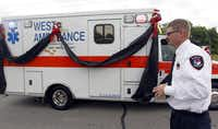 A West ambulance, adorned with black ribbon in memory of victims of last week's deadly explosion, rolls past Powell, Texas firefighter Kyle Ware Thursday in West. The ambulance was part of a procession to a memorial service at the Ferrell Center in Waco.