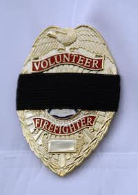A black mourning band covers the badge of a volunteer firefighter participating in Thursday's procession and memorial sevice honoring victims of last week's deadly fertilizer explosion in West.