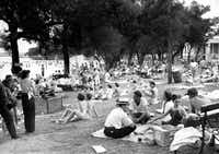 People relax and enjoy the sun at White Rock Lake bathing beach on July 4, 1946.