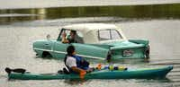 David Shappard of Mesquite waves to kayaker Kevin Harbolt of Carrollton while taking his amphibious 1964 Amphicar for a spin on White Rock Lake in November 2004.