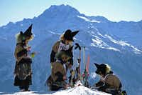 Participants prepare cheese raclettes during the 30th edition of the Belalp Witches Ski Race on January 14, 2012 in Belalp, Switzerland.