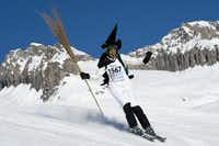 """A skier disguised as witches participates in the 30th ski downhill race at Belalp-Blatten, Southwestern Switzerland, Saturday, Jan. 14, 2012. The downhill at Belalp is a fun event called """"Hexenabfahrt"""" (downhill of the witches) and many of the 1,500 participants race down the 12km slope long in colorful costumes."""
