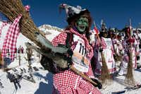 """A group of skiers disguised as witches participate in the 30th ski downhill race at Belalp-Blatten, Southwestern Switzerland, Saturday, Jan. 14, 2012. The downhill at Belalp is a fun event called """"Hexenabfahrt"""" (downhill of the witches) and many of the 1,500 participants race down the 12km slope long in colorful costumes."""