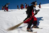 """A group of skiers disguised as witches participate in the 30rd ski downhill race at Belalp-Blatten, Southwestern Switzerland, Saturday, Jan. 14, 2012. The downhill at Belalp is a fun event called """"Hexenabfahrt"""" (downhill of the witches) and many of the 1,500 participants race down the 12km slope long in colorful costumes."""