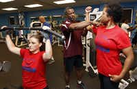 Fitness instructor Floyd Williams, center, of fitness ministry of Oak Cliff Bible Fellowship, assists church member Vonetta Watson, right, as Heather Gregory exercises.