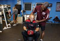 Fitness instructor Floyd Williams, standing, of fitness ministry of Oak Cliff Bible Fellowship, talks with a community member Eric Jones while Jones visit to the gym for an exercise