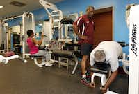 Fitness instructor Floyd Williams, standing, of fitness ministry, watches as a community member Elizabeth Wimbley participates in her exercise at Oak Cliff Bible Fellowship Church.