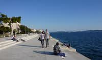 The 'Riva' in Zadar, Croatia attracts locals and visitors alike, with its views over the water and its award-winning sea organ. The small circular openings in the cement walkway are where sounds emerge as waves hit 35 organ-style pipes installed under the steps. The pipes are of different sizes and positioned at different angles so they each produce different sounds.