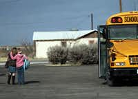 Joni Lindsay gives Tracy Putnam, 11, a hug as she gets off the school bus in front of the Loving County Court House in Mentone. Tracy is one of only 11 schoolchildren who live in Loving County. The children take a 32-mile bus ride to get to school in neighboring town of Wink.
