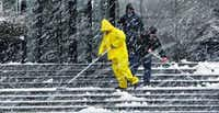 For some, the wintry conditions were more about work than play. Workers at the Capital One Bank building on Pearl Street in downtown Dallas tried to keep the building's steps clear of snow and sludge Thursday.
