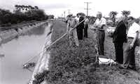 A group of men stands at the site where Irene Garza's body was found in April 1960 in an irrigation ditch about a mile from her church. (1960 File Photo/McAllen Police)