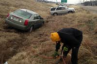 Mark Leismer connects a tow chain to a friend's car that slid off Highway 67 Tuesday morning in Cedar Hill as icy conditions that made a mess of Monday evening's commute continued to cause problems.David Woo - Staff Photographer