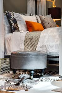 Cody Hutcheson of the Codarus designer showroom in Dallas' World Trade Center designed a master bedroom in warm tones using natural woods and fine linens. The upholstered silver footstool is begging for bedside books.