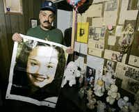 Felix DeJesus holds a banner showing his daughter, Gina DeJesus, while posing with a memorial in his living room in March 2004 in Cleveland. Gina DeJesus, who went missing in 2004, and two other women -- Amanda Berry, missing since 2003, and Michelle Knight, missing since 2002 -- were rescued Monday from a home near downtown Cleveland where police belive they were tied up for most of the years they spent missing.(Tony Dejak - The Associated Press)